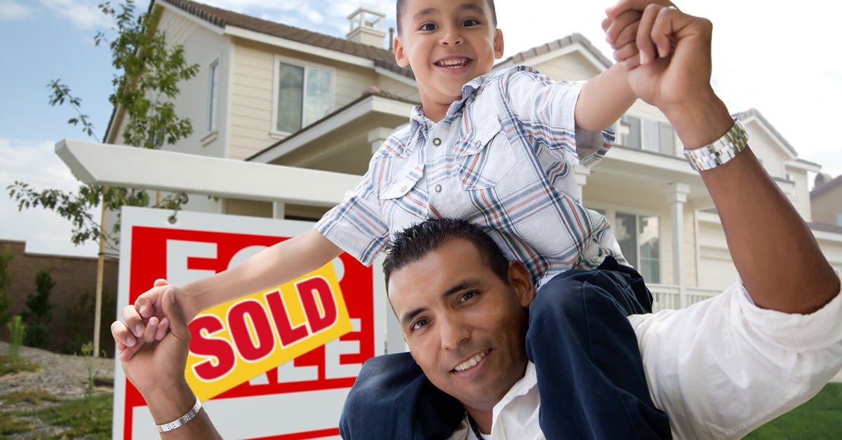 Father and Son with Sold Sign in Background
