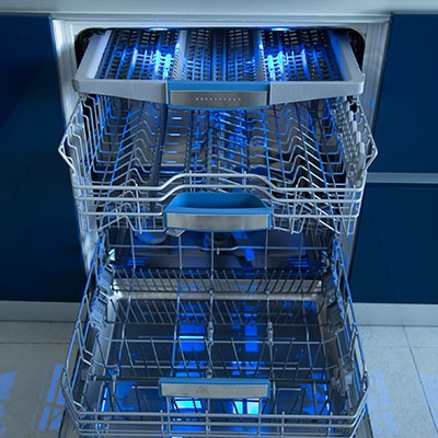 An open dishwasher with blue lighting on a blue background.