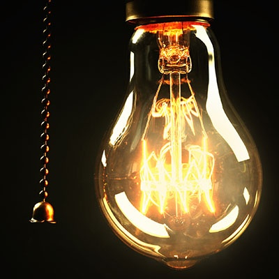 A light bulb with the electrical switch in the on position against a black background.