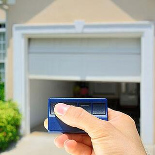 A man pressing the button on his automatic garage door opener.