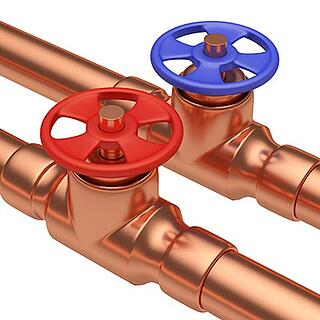 Copper plumbing pipes with hot and cold valves.