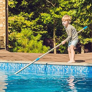 Small boy cleaning a backyard swimming pool.