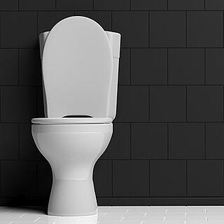 White porcelain toilet in a bathroom with gray subway tiles behind it.